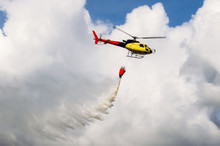 Helicopter Flying In The Sky Pouring Water On Fires.