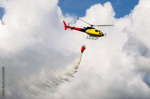 Tuinposter Helicopter Helicopter flying in the sky pouring water on fires.