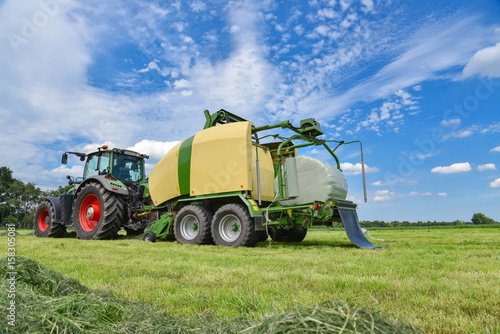 Grasernte , Traktor mit Großballenpresse und Folienwickler im Einsatz Canvas Print