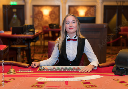 Photo Cute lady casino dealer at poker table.