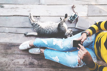 Hipster Lifestyle - Girl In Jeans With Black Smartphone And Retro Camera With Cat Sit On The Wooden Floor. Vintage Film Color Effect And Retro Color Style