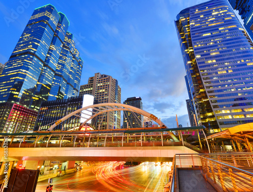 Photo  View of a pedestrian overpass in downtown of Bangkok City with high rise buildings in the background in evening light