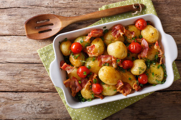 Baked new potatoes with bacon and tomatoes close-up in a baking dish. Horizontal top view