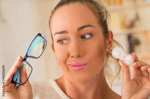 Young blonde woman holding contact lens case on hand and holding in her other hand a blue glasses on blurred background Canvas Print
