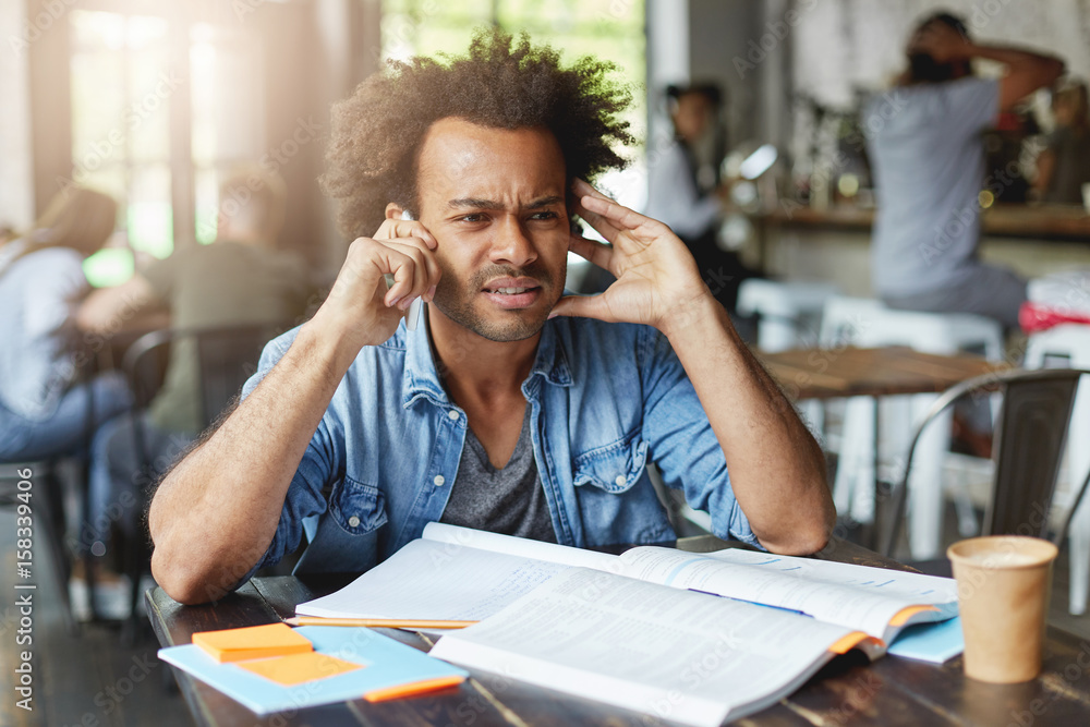 Fototapeta Hipster dark-skinned Afro American male with curly dark hair wearing denim shirt sitting at noisy cafeteria trying to hear voice over smartphone having bad conncetion working with books and writing