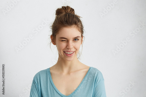 Cute young female with delicate features having hair tied in knot wearing blue sweater blinking her eyes with pleasure having happy expression Canvas Print