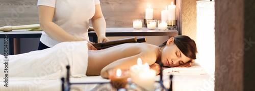 Fototapeta oman having bamboo stick massage at day spa obraz