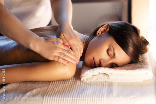 Tuinposter Spa Body massage and spa treatment in modern salon with candles