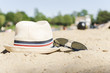 Hat and sunglasses on sand at the sity lake background.