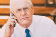 Serious Senior Businessman with Smartphone