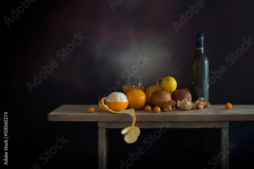 Fotomural  Oranges peel off and other fruits on and old bottle on the plank in dim light night / Still life style  and select focus, space for text