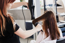 Hairdresser Dries Hair With Hairdryer In Beauty Salon
