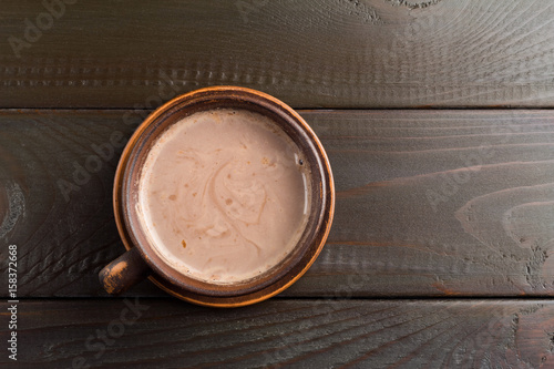 Foto op Plexiglas Chocolade Hot chocolate or cocoa drink in clay cup, on dark brown wooden table, top view