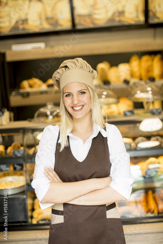 Foto op Plexiglas Bakkerij Beautiful young woman smiling confidently posing in her baker shop