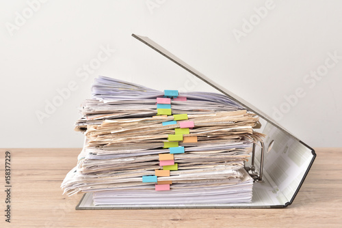 Fotografía  Pile of Financial documents with colorful clips on wood desk stack up,back isola