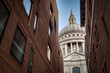 World renowned landmark that is St. Paul Cathedral seen from a narrow alley enclosed by two brick buildings on a sunny day of summer in London, England, UK