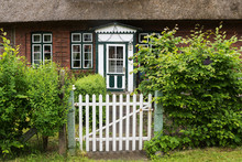 Garden Gate And A Beautiful Old Wooden Front Door In Green And White On A Typical Traditional Thatched Roof House In Northern Germany, Europe