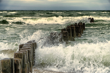 Fototapeta Do biura Wooden breakwater in the stormy sea. Seascape, Baltic sea near Klaipeda, Lithuania.