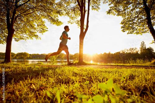 Plakat Młodego człowieka bieg w parku podczas zmierzchu