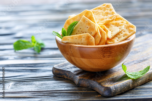 Vászonkép Crispy crackers with salt in a wooden bowl.