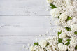 Wooden background with flowering branches of white lilac and viburnum flower