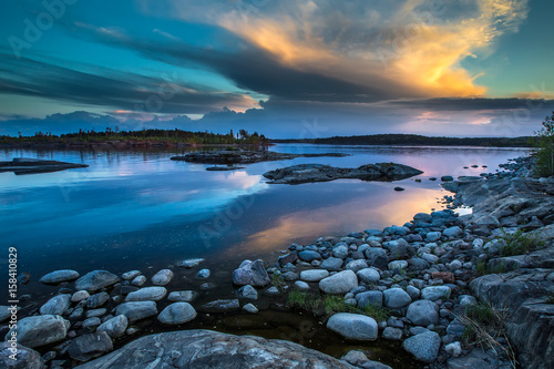 There are many stones near the shore. Reflection of the sky in the water. Northern landscape. Wild nature of the north. Karelia. Ladoga lake.