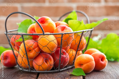 Fresh apricots with leaves in basket on wooden table Wallpaper Mural