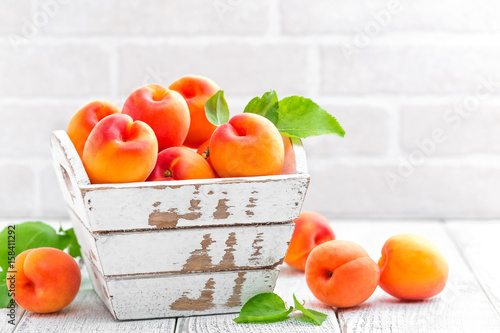 Fresh apricots with leaves on white wooden background Fotobehang