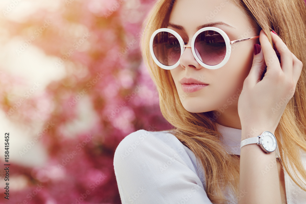 Fototapety, obrazy: Outdoor close up portrait of young beautiful fashionable girl posing in street. Model wearing stylish white round sunglasses, wrist, hand watch. Female fashion concept. Copy, empty space for text