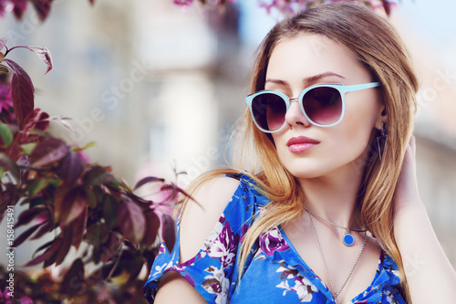 Outdoor close up portrait of young beautiful fashionable