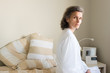 Middle aged woman in white bathrobe seated on bed looking at camera (selective focus)