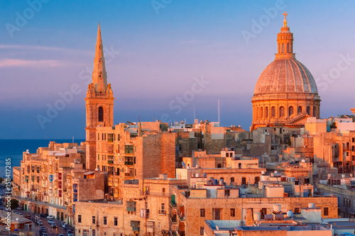 Poster de jardin Europe Méditérranéenne View from above of the domes of churches and roofs at beautiful sunset with churches of Our Lady of Mount Carmel and St. Paul's Anglican Pro-Cathedral, Valletta, Capital city of Malta