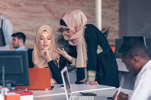 Two woman with hijab working on laptop in office. Fototapeta