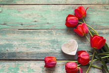 Background With Red Tulips And Wooden Heart On Old Wooden Boards.