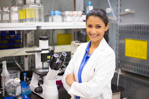 Fotografia  Closeup portrait, young smiling scientist in white lab coat standing by microscope