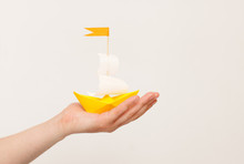 Paper Boat In Hand On White Background