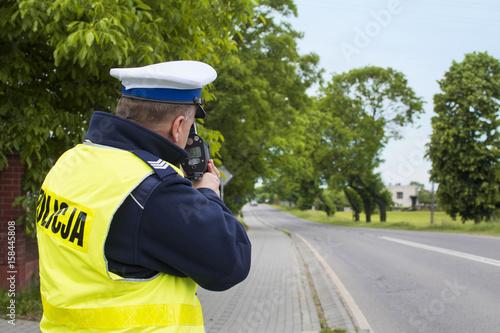 Kontrola radarowa przy drodze wojewódzkiej. Policjant dokonuje pomiaru prędkości w terenie zabudowanym.