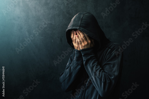 Desperate man in hooded jacket is crying Fototapeta