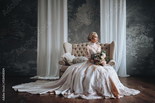Carta da parati Beautiful bride in a cream wedding dress with a wedding bouquet, with orange and white flowers