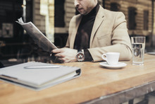 Handsome Elegant Caucasian Businessman Sitting At Coffee Shop And Reading Newspapers.