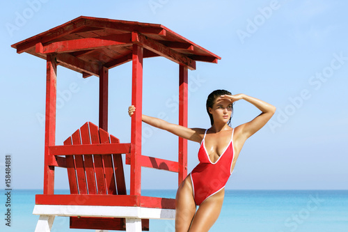 Sexy woman in red swimsuit beside lifeguard tower Canvas Print