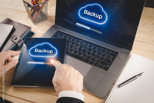 Fotografie, Obraz Businessman backup data from laptop and tablet device to cloud service
