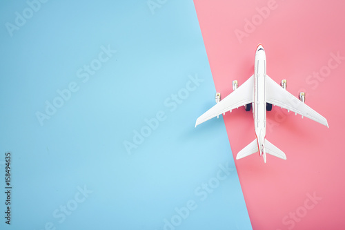 Türaufkleber Flugzeug Flat lay design of travel concept with plane on blue and pink background with copy space.