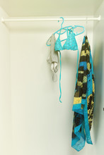 Swimsuit Hanging On Rail In White Wardrobe. Blue Stripped Bikini And Flip Flop Sandals. Sunny Toned