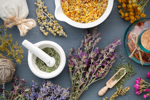 Medicinal herbs, mortar of healing herbs, sachet and bottle of drugs on wooden table Canvas Print