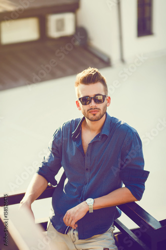 Young Male Model Posing Outdoors In Blue Shirt And Sunglasses Buy This Stock Photo And Explore Similar Images At Adobe Stock Adobe Stock