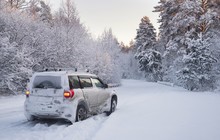 Off-Road Winter Adventure, White SUV Car On Road With Much Snow In Winter Pine Forest. White Crossover Covered With Snow On The Road Among The Winter Forest. Car And Falling Snow In Winter