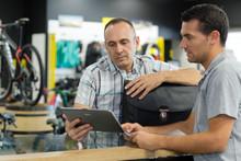 Man Working In Bike Rental Shop Dealing With Customer