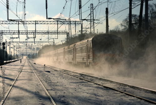 A passenger train goes by rail in winter Canvas Print