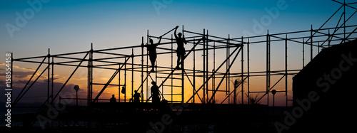 Fototapeta Construction workers working on scaffolding.